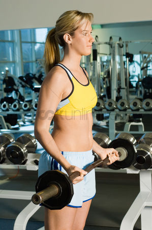Ponytail : Woman using barbell in gymnasium