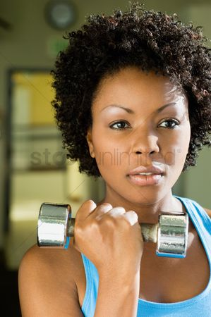 Dumbbell : Woman using dumbbell indoors  close-up   portrait