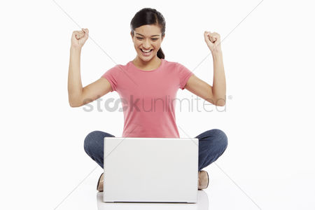 Smiling : Woman using laptop and cheering