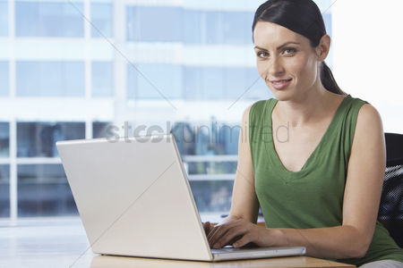 Office worker : Woman using laptop at desk in office portrait