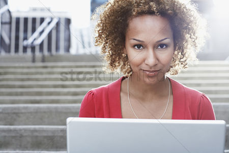 Curly hair : Woman using laptop on steps close-up portrait