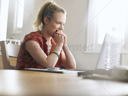 One person : Woman using laptop sitting at dining table low angle view