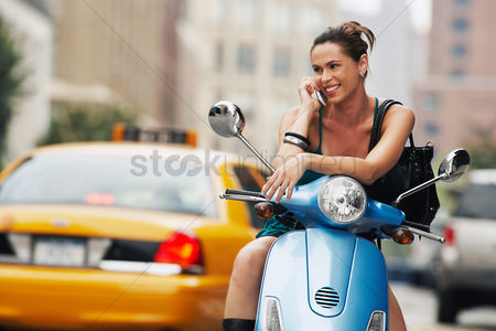 Cell phone : Woman using mobile phone on moped