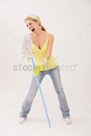 Housewife : Woman using mop as microphone