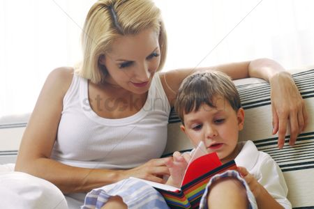 Eastern european ethnicity : Woman watching her son reading a book