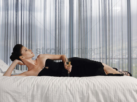 Fashion : Woman wearing elegant dress lying on bed with champagne glass in bedroom