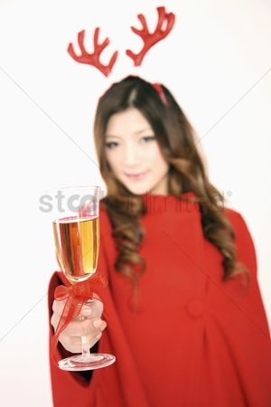 Toasting : Woman wearing reindeer antler toasting with champagne