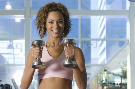 Posed : Woman weightlifting with dumbbell