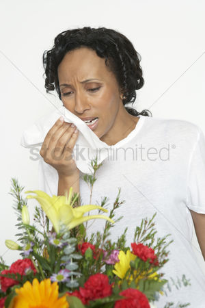 Count : Woman with allergy holding tissue near flowers studio shot