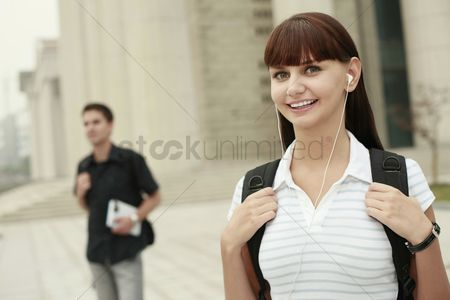 Eastern european ethnicity : Woman with backpack listening to music on portable mp3 player