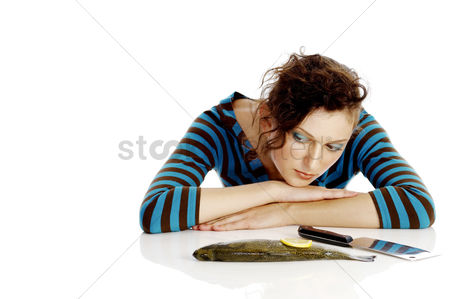 Worry : Woman with fish and knife on the table