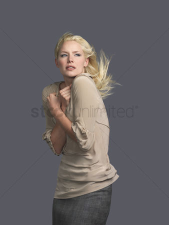 Blowing : Woman with hair blowing arms crossed side view