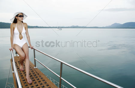 Contemplation : Woman with hat and sunglasses sailing on yacht