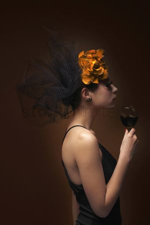 Elegance : Woman with net and flower decorating her hair holding wine glass