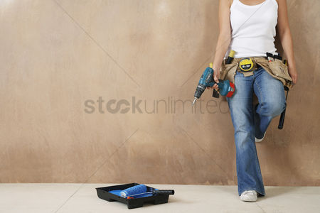 Denim : Woman with toolbelt and drill leaning against wall low section