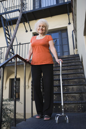 Stairs : Woman with walking cane outside house