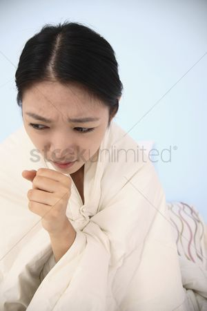 Frowning : Woman wrapped in blanket  coughing