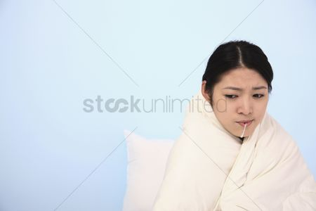 Thermometer : Woman wrapped in blanket with thermometer in her mouth