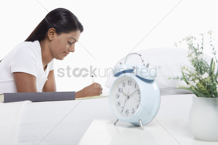 Malaysian indian : Woman writing notes while laying on bed