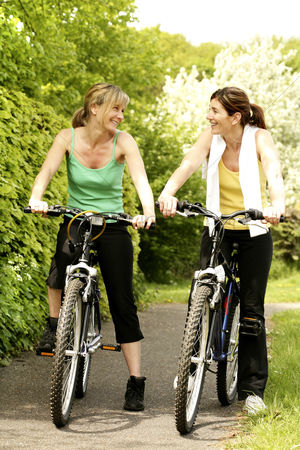 Outdoor : Women chatting while sitting on bicycles