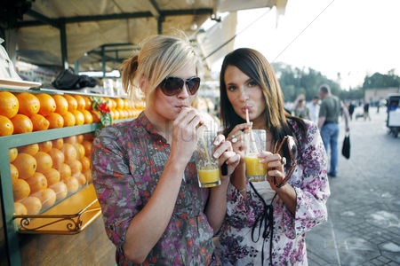Fashion : Women enjoying fresh orange juice at beverage stall