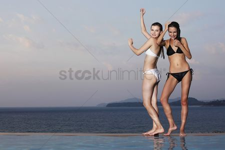 Arm raised : Women posing at the edge of pool