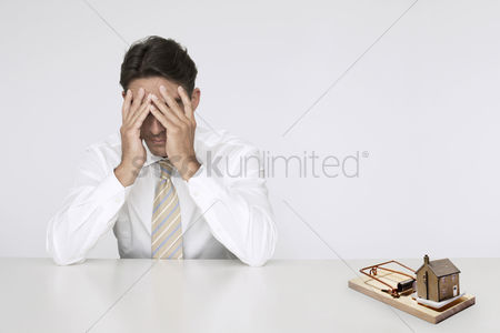 Conceptual : Worried businessman at table model home in mouse trap representing expensive real estate costs
