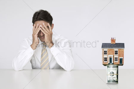 Us : Worried businessman at table with house on top of bills representing increasing real estate rates