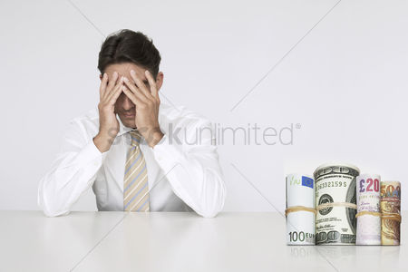 British ethnicity : Worried businessman at table with money rolls representing financial problems