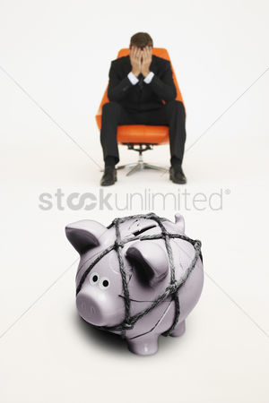 Rope : Worried businessman on chair and piggybank tied with rope representing financial difficulties