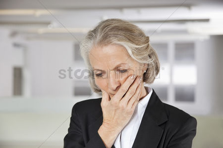 Wondering : Worried senior businesswoman with hand on mouth in office
