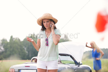 On the road : Worried woman using cell phone while friend examining broken down car outdoors