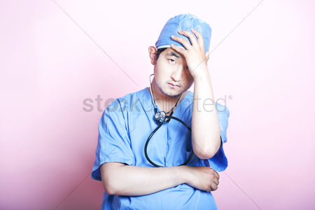 British ethnicity : Young  asian surgeon wearing scrubs and looking stressed