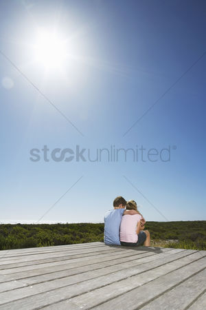 Land : Young boy with arm around young girl sitting on boardwalk