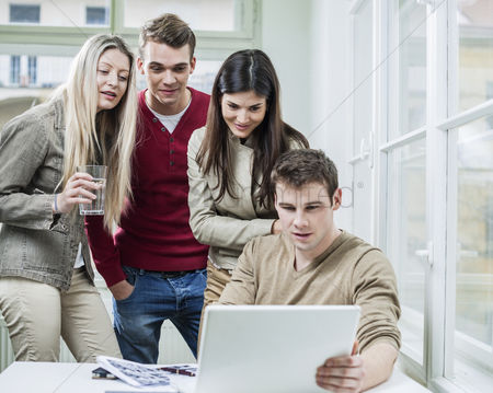 Three quarter length : Young business people looking at laptop in meeting