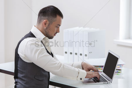 Employee : Young businessman using at laptop at desk