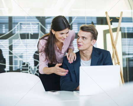 Office worker : Young businessman with female colleague discussing over laptop at table in office