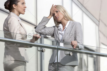 Employee : Young businesswoman arguing with female colleague at office railing