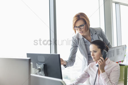 Two people : Young businesswoman using landline phone while colleague pointing at computer monitor in office