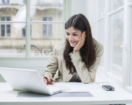 Czech republic : Young businesswoman using laptop at office desk
