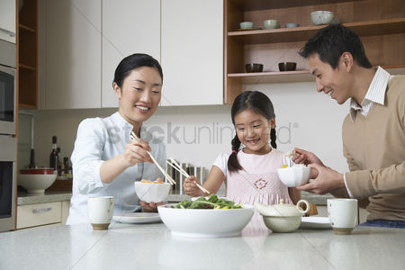 Bowl : Young couple and daughter eating a meal with chopsticks on kitchen counter