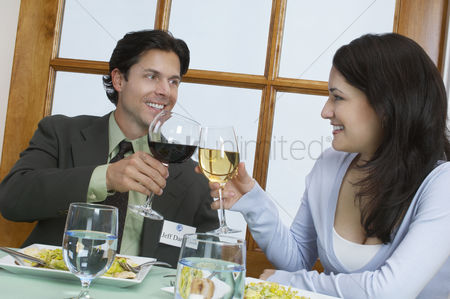 Toasting : Young couple at restaurant table toasting with wine