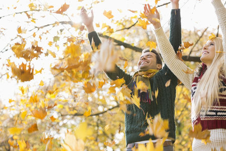Girlfriend : Young couple enjoying falling autumn leaves in park