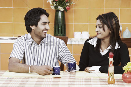 Tea pot : Young couple having tea at the dining table