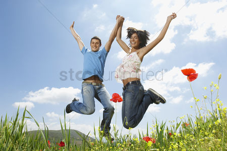 Two people : Young couple jumping for joy in mountain meadow portrait low angle view