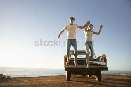 Truck : Young couple jumping from back of van parked by ocean