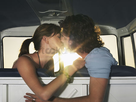Interior : Young couple kissing in front seat of camper van