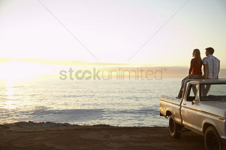 Young woman : Young couple sitting on van parked in front of ocean