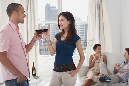 Toasting : Young couples drinking wine in living room