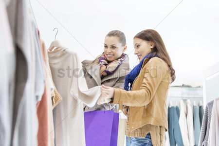 Fashion : Young female friends choosing sweater in store